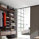 Begehbarer und beleuchteter Kleiderschrank von Ars Nova Collection Centric in Nussbaum mit Schiebetür – Blick ins angrenzende Schlafzimmer.