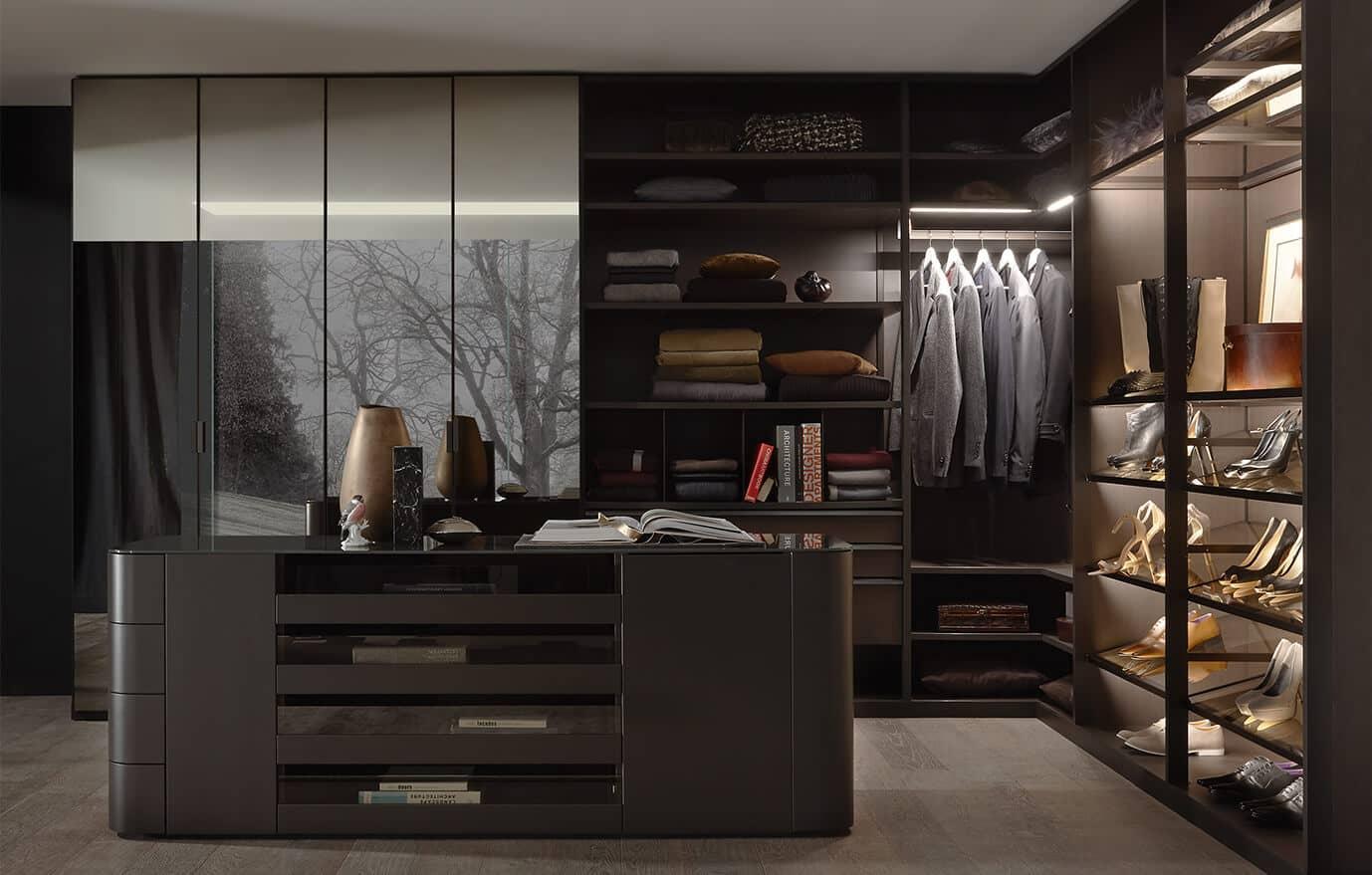 Begehbaren Kleiderschrank Walk_in von Ars Nova Collection mit freistehender Kommode, verspiegelten Schiebetüren und einem beleuchteten Eck-Schrankelement.
