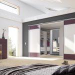 Begehbarer Kleiderschrank von Geha Möbel mit Raumteilertüren aus lichtdurchflutetem Milchglas und Akzenten in weinrot..