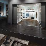 Begehbarer und beleuchteter Kleiderschrank von Geha Möbel mit Raumteilertüren aus Klarglas und Glastüren in Anthrazit. Korpus und Raumteilertüren frei gestaltbar.