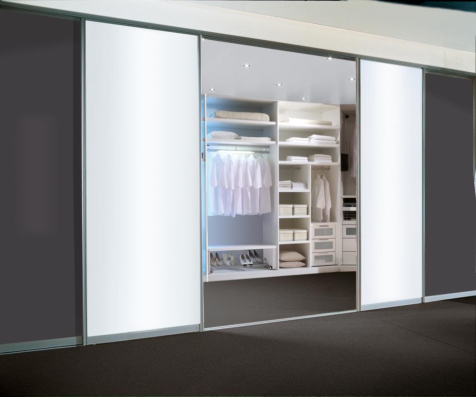 Begehbarer Kleiderschrank von Geha Möbel mit Raumteilertüren aus lichtdurchflutetem Milchglas.